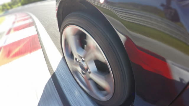 Car wheel spinning while driving fast at a race track, finishing a lap video