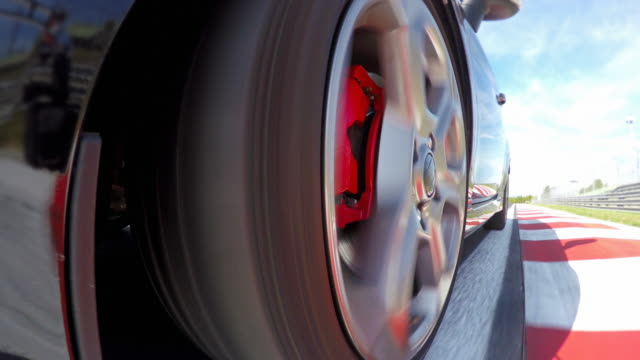 Car wheel spinning while driving fast at a race track, training for competition round video