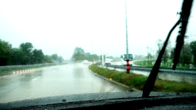 Car windshield wiper are removing rain while driving on the road in the bad weather day video