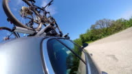 Car with two mountain bikes on bicycle roof rack driving on a winding coastal road in the summer video