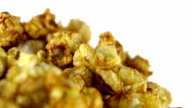 Caramel popcorn rotates on a white background. Super close up shot video