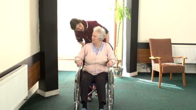 Care / Nursing home Nurse assisting elderly patient in Wheelchair video
