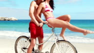 Carefree couple going on a bike ride on the beach video