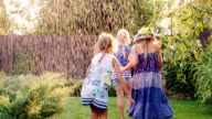 Carefree fun children play in the garden. Laughing, running under the jets of water or rain video