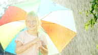 Carefree girl five years rejoices summer rain. standing under a colored umbrella video