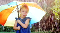 Carefree girl three years under the umbrella of color. Hiding from the rain video