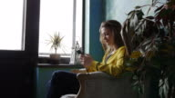 Carefree positive brunette sitting in an armchair with a smartphone video