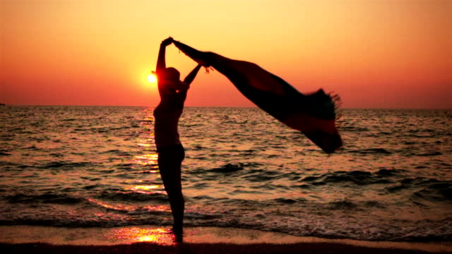 Carefree Woman On The Beach Holding Scarf At Sunset video