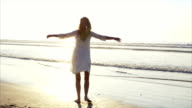 Carefree woman turning and twirling around on beach video