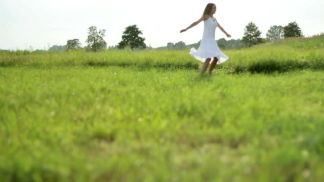 Carefree young woman on the grass, slow motion video