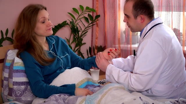 Careful male doctor checking pulse and examining female patient with stethoscope video