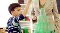 Careful mixed race schoolboy stacks plastic cups at school video