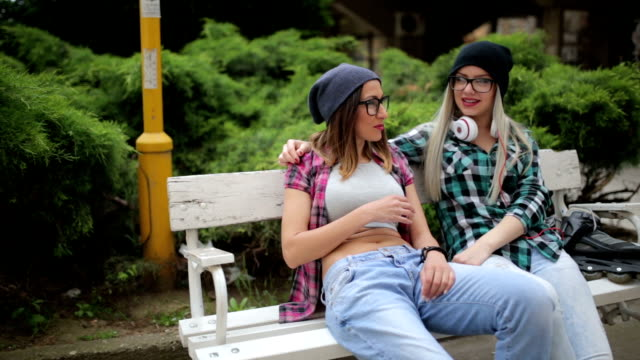 Careless girlfriends laughing at the park on the bench video