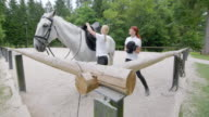 DS Caretaker tacking up a white horse for the rider video