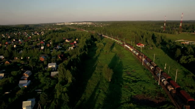 Cargo trains moving through the village, aerial view video