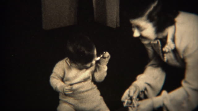 1937: Caring mother and baby unwrap gift together, drops doll on floor. video