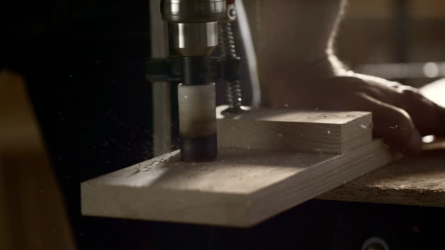 Carpenter drilling a hole in a wood plank video