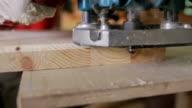 Carpenter grinds board grinding machine. close-up video