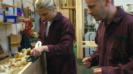 Carpenter in workshop advising female apprentice as she planes length of wood at work bench video