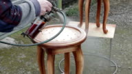 Carpenter is covering stool by lacquer video