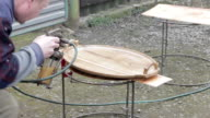 Carpenter is covering wooden platter by lacquer video