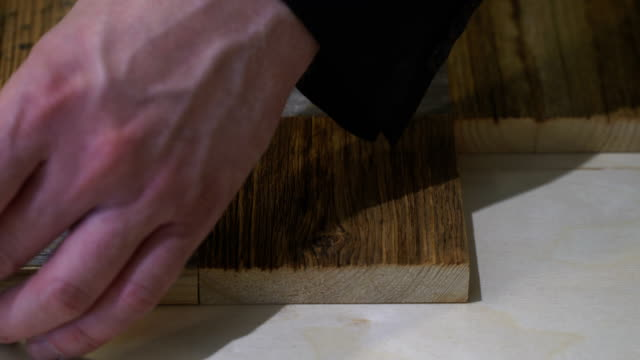 Carpenter labor master work with wood. Master puts and sticks squares from old wood in chessboard order. Master's hands closeup video