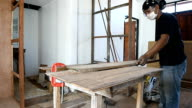 carpenter man use a circular saw table for cut wood plank video