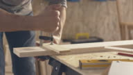 Carpenter removing clamp from pieces of wood video