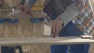 Carpenter sanding wood block in workshop video