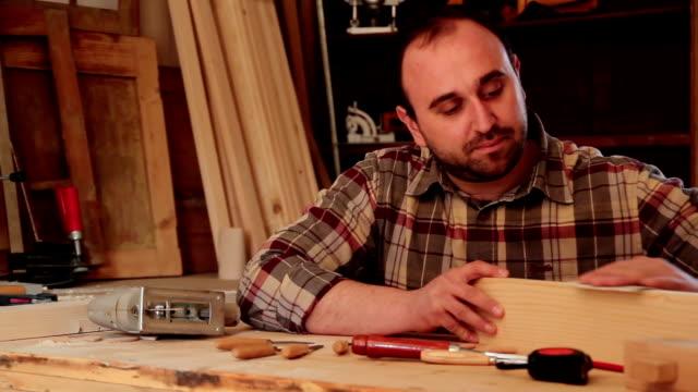 Carpenter sanding wood in his workshop video