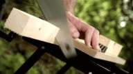 Carpenter sawing a wooden square with a wood saw video