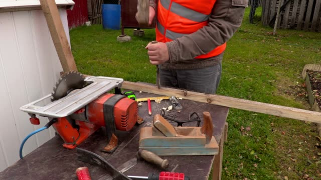 Carpenter using hammer and chisel at the working table video