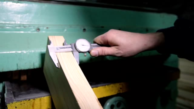 Carpenter with calipers measuring wood in workshop video