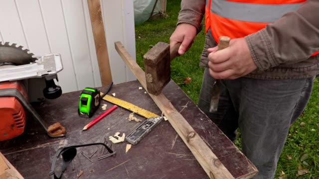 Carpenter with hammer and chisel video