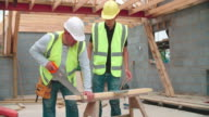 Carpenter With Male Apprentice Cutting Wood On Building Site video