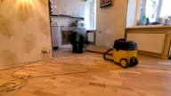 carpenter worker cleaning room after installing wood parquet board during flooring work timelapse video