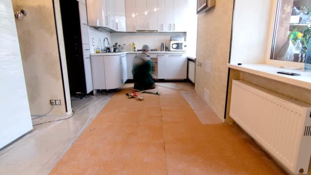 carpenter worker installing wood parquet board during flooring work timelapse video