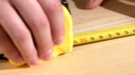 Carpenter worker using roulette on wooden plank, slow motion, close up video