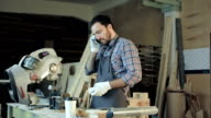 Carpenter working on his craft in a dusty workshop and speak phone video