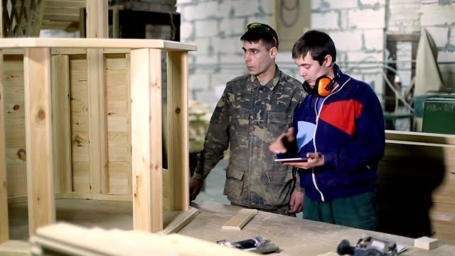 Carpenters using digital tablet in workshop video