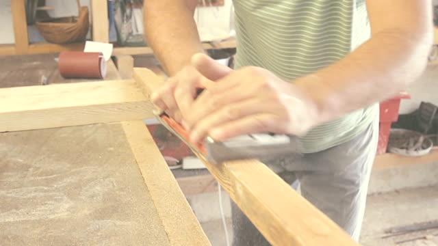 Carpenter's working on raw wood in little dusty workshop. video