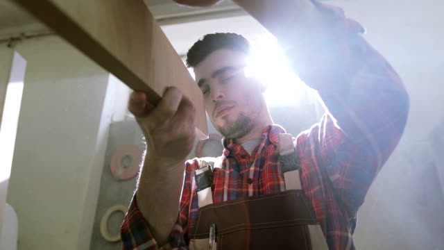 4K Carpentry. Joiner checking a sawing quality of wooden board. video