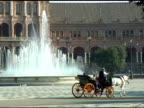 Carriage passing fountain at Plaza de Espana Seville Spain video