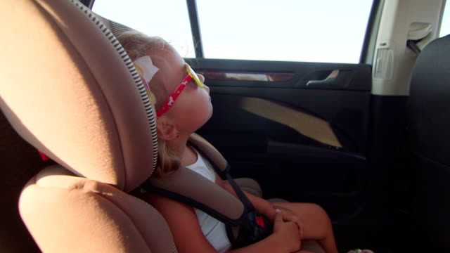 Carrying little girl passenger in car child forward-facing seat with harness video