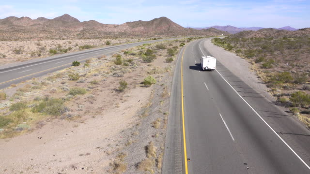 Cars and camper driving on busy highway, freight semi trucks transporting goods video