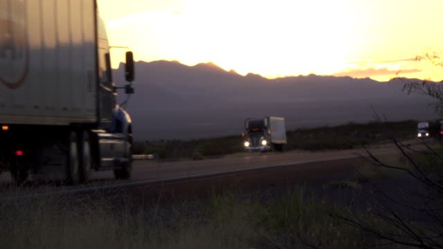 Cars and freight transporting trucks driving on busy highway after the sunset video