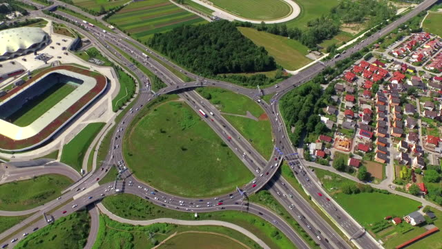 AERIAL: Cars and trucks driving on highway roundabout intersection video