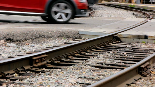 Cars cross rail road tracks at a railway station crossing zone. video