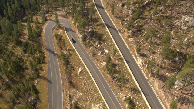 AERIAL Cars driving along the snaking road up the forested mountain pass highway video