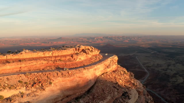 AERIAL Cars driving on switchback road along the red rock desert cliff at sunset video